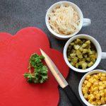 Schneidebrett mit Petersilie und drei weiteren Zutaten für den Salat